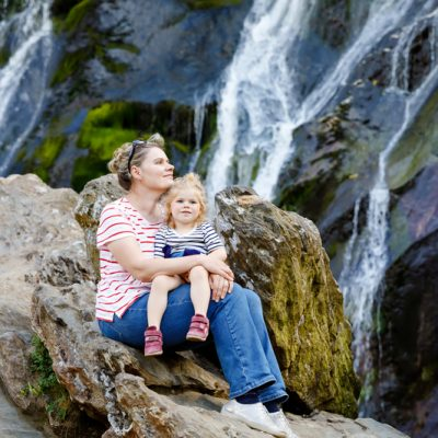 Cute toddler girl and mother sitting near water cascade of Powerscourt Waterfall, the highest waterfall in Ireland in co. Wicklow. Family time vacations with small children. Woman and baby child.